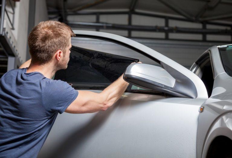 Applying tinting foil on a car window in a garage