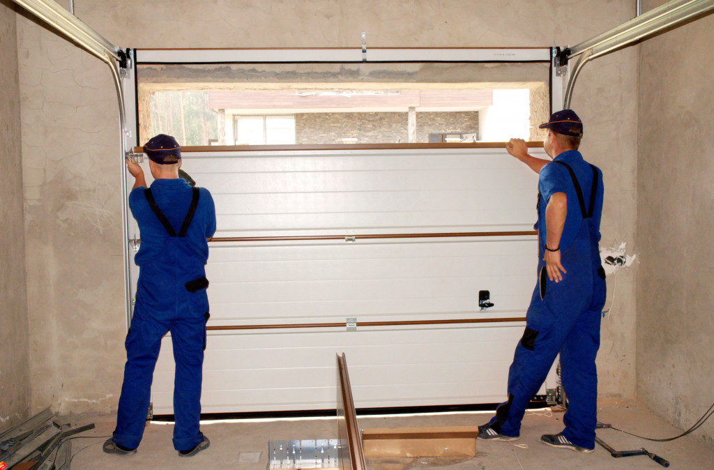 men repairing a garage door