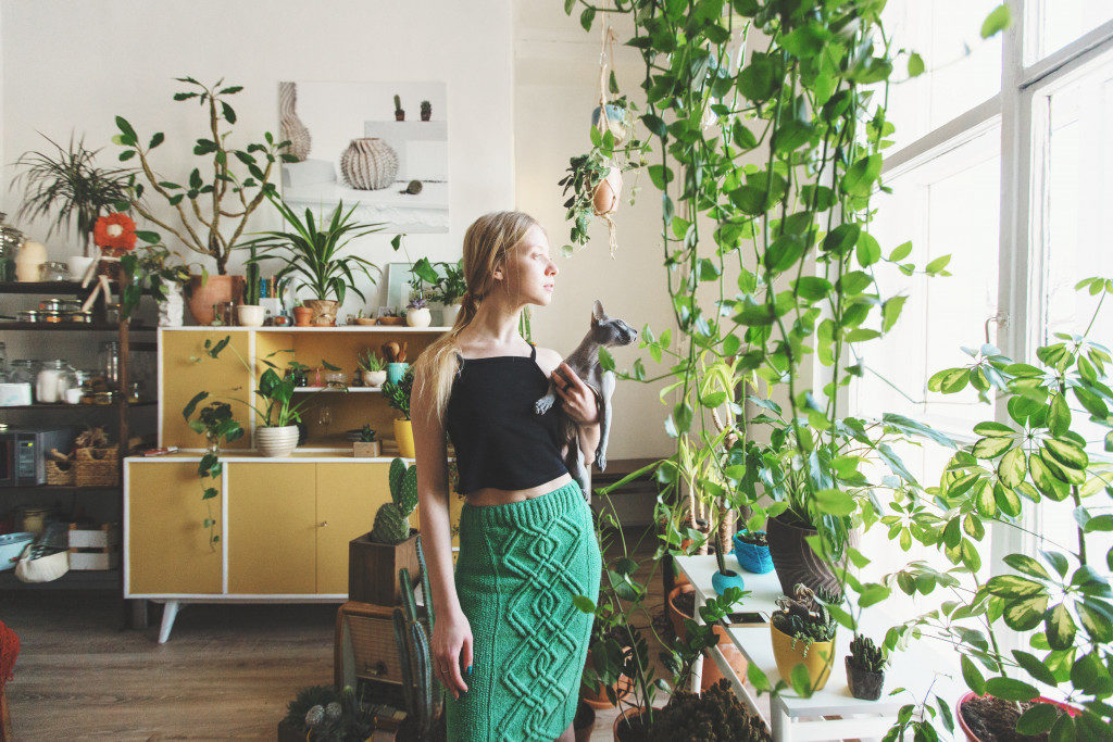 woman with cat and her house filled with houseplants
