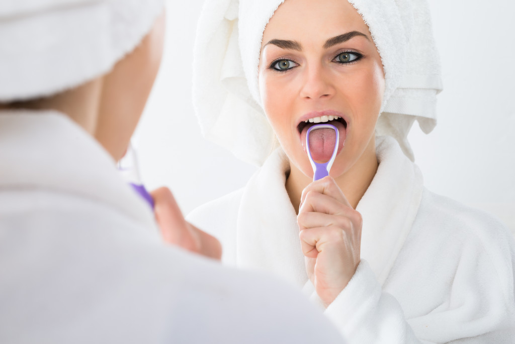 Close-up Of A Woman Looking In Mirror Cleaning Her Tongue