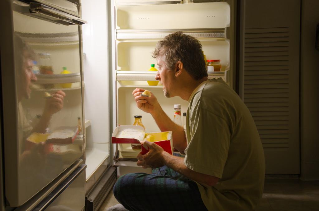 man binge eating in fridge